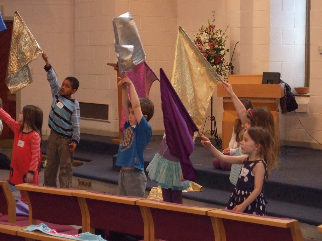 Children's worship with flags.
