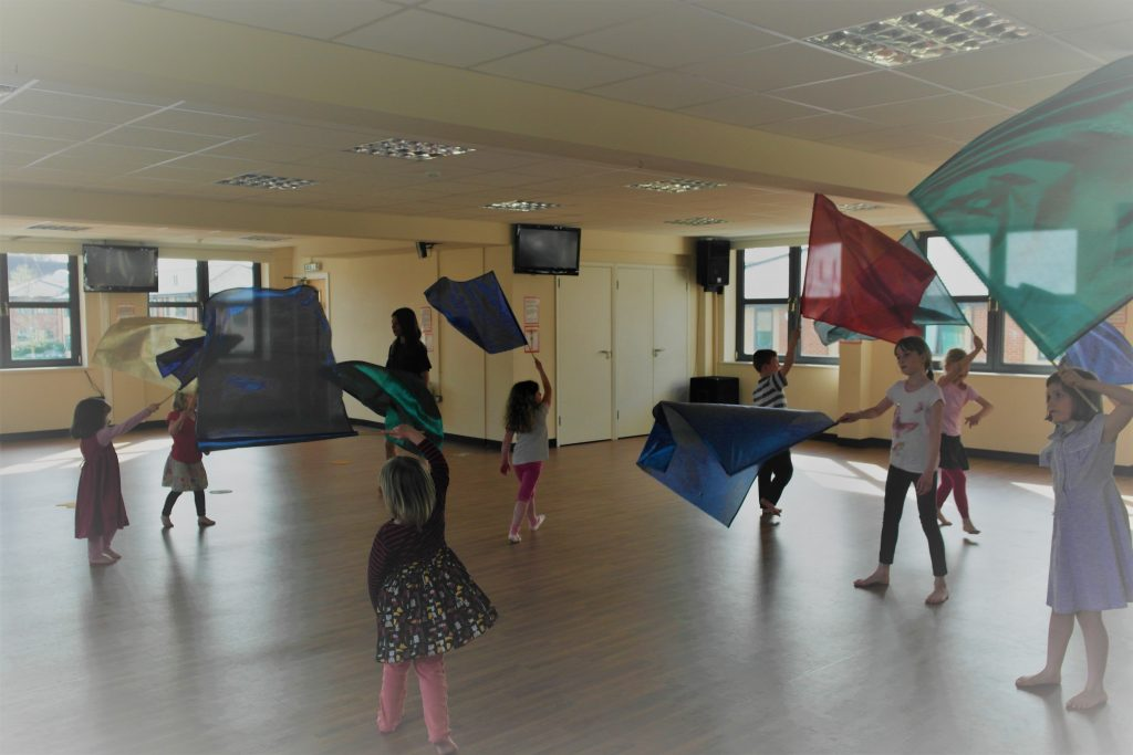 Indoor group during children's worship using flags.