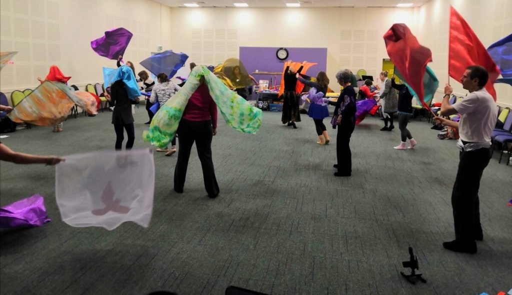 Group of worship dancers moving with worship flags.
