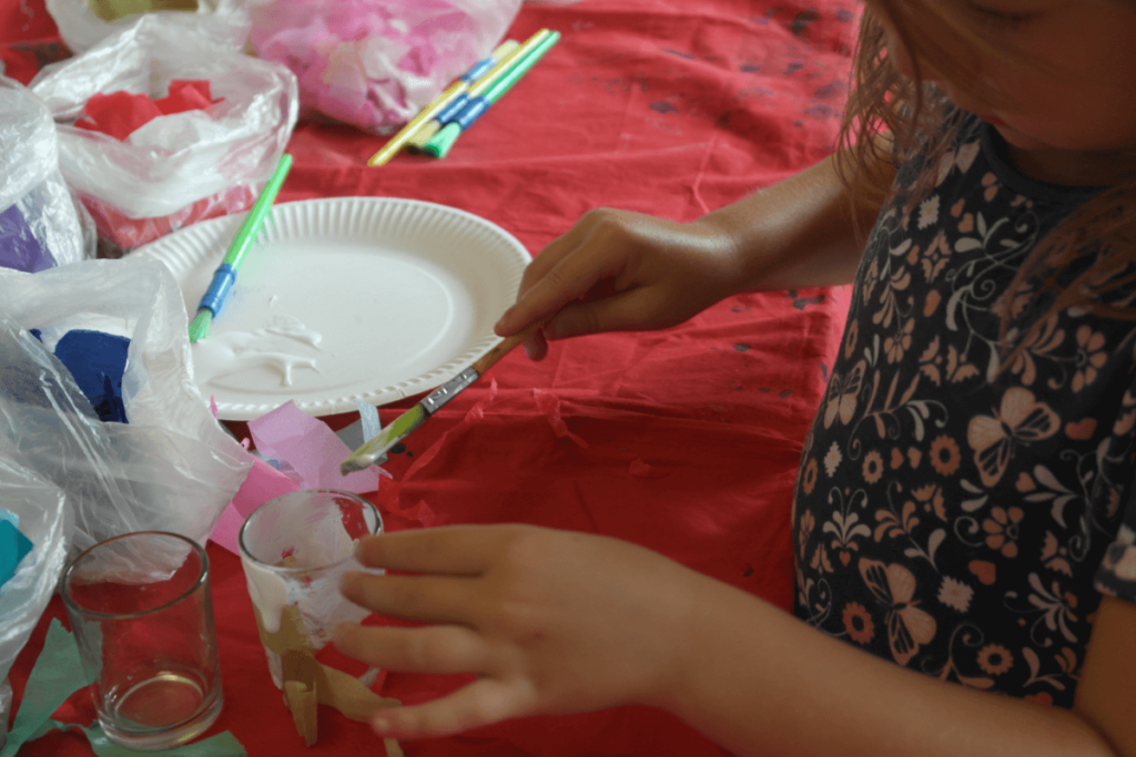 Sticking tissue paper onto glass jars during craft time at a kids worship dance session.