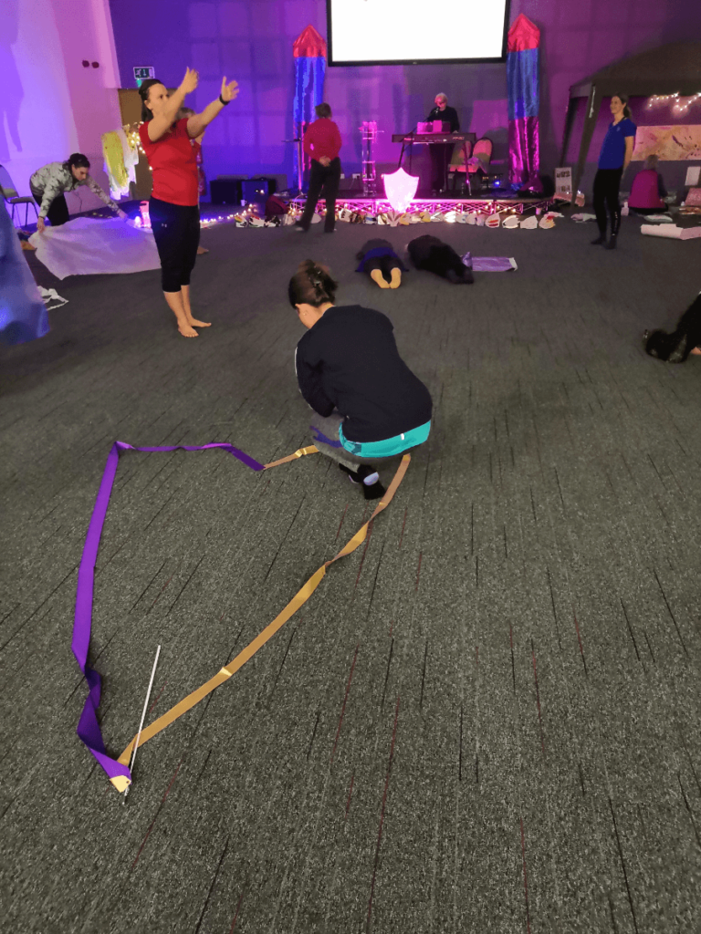 Heart shape on floor with ribbons. Person praying.