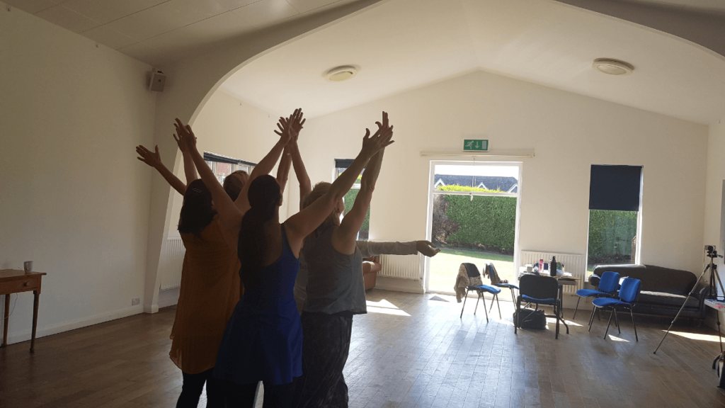 A group of dancers reaching with their arms up all close together.